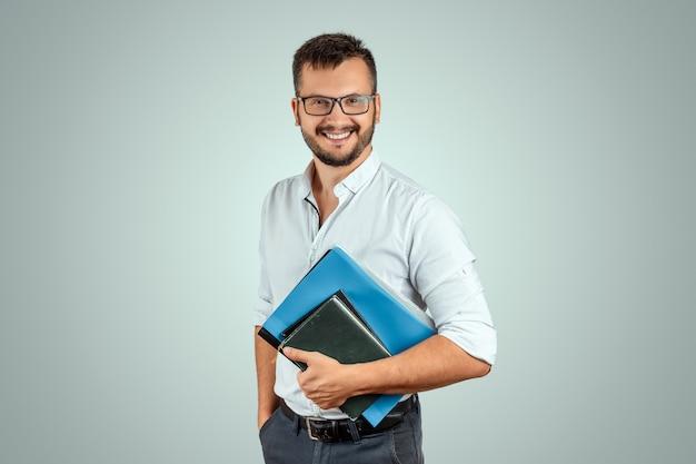 Portret van een jonge mannelijke leraar op een lichte achtergrond