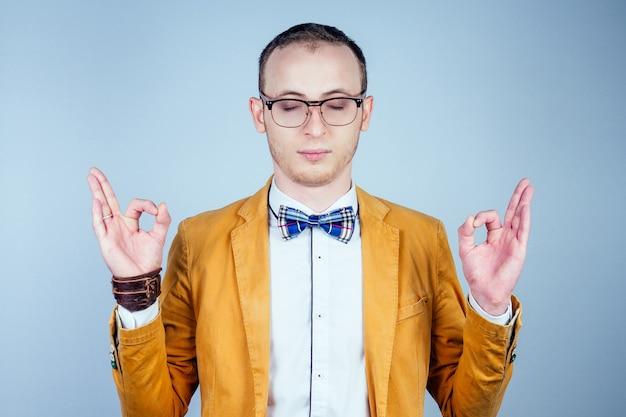 Portret van een jonge mannelijke nerd met een bril, in een stijlvol pak en stropdas mediteert