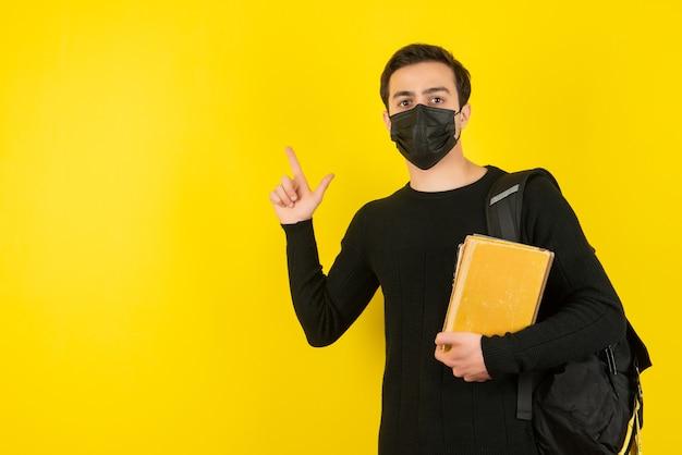 Portret van een jonge mannelijke student met een medisch masker die universiteitsboeken op een gele muur houdt