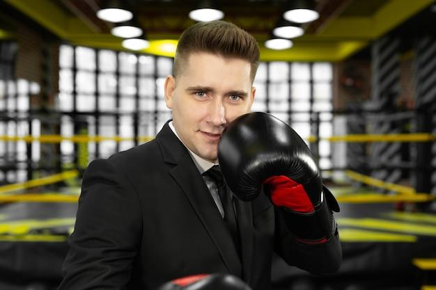Portret van een jonge mannelijke zakenman in bokshandschoenen, die de camera bekijkt.