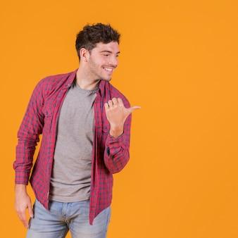 Portret van een jonge mens die zijn duim toont aan kant tegen een oranje achtergrond