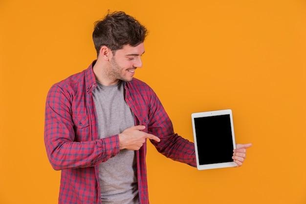 Portret van een jonge mens die zijn vinger op digitale tablet richt tegen een oranje achtergrond