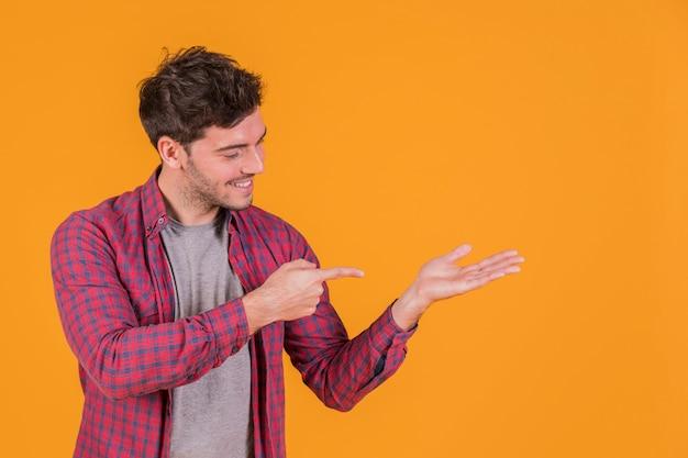 Portret van een jonge mens die zijn vinger op hand tegen een oranje achtergrond richt