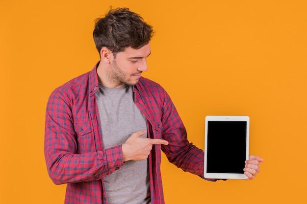 Portret van een jonge mens die zijn vinger richt op digitale tablet tegen een oranje achtergrond