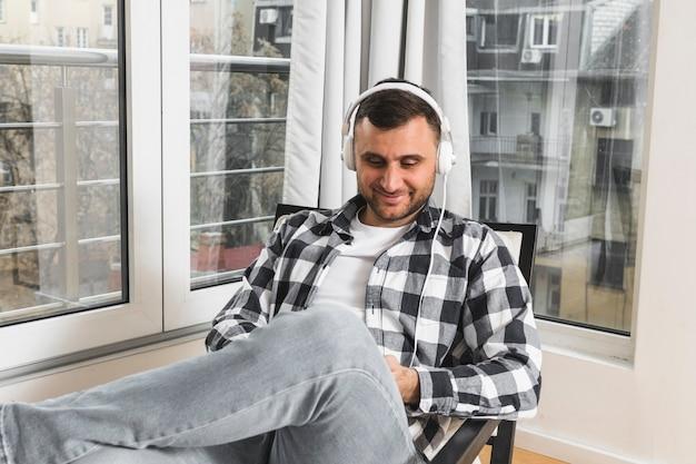 Portret van een jonge mens het luisteren muziek op hoofdtelefoon dichtbij het venster
