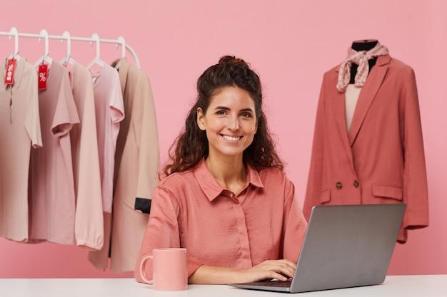 Portret van een jonge modeontwerper aan de tafel zitten en glimlachend in de camera die ze met behulp van laptopcomputer