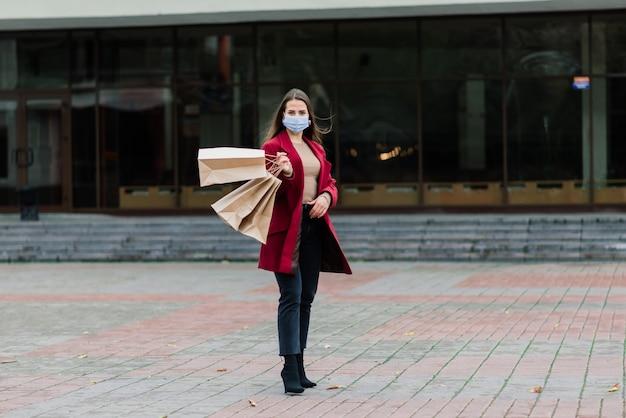 Portret van een jonge modevrouw die een beschermend masker draagt met boodschappentassen op straat in de stad