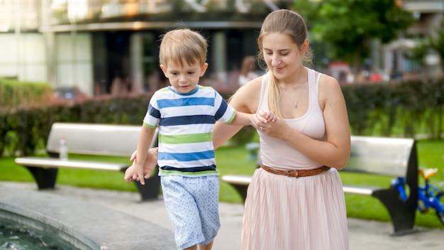 Portret van een jonge moeder die haar 3-jarige peuterjongen vasthoudt en ondersteunt tijdens het wandelen in het park