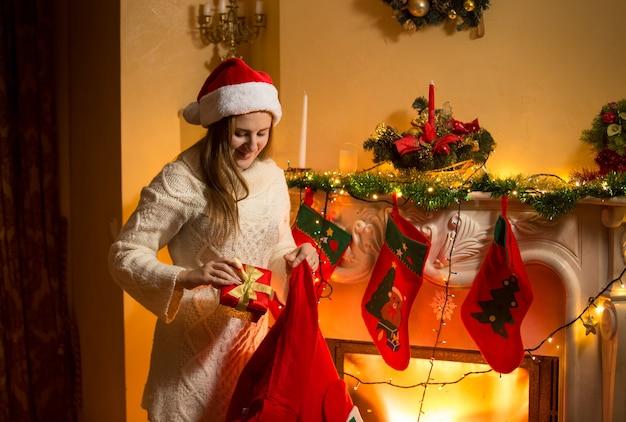 Portret van een jonge moeder die kerstcadeaus in kousen steekt die aan de open haard hangen