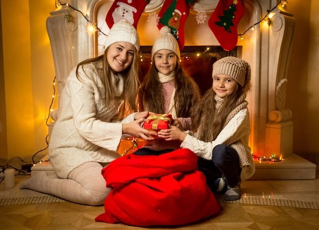 Portret van een jonge moeder die met kerstmis naar een cadeau in een grote rode zak kijkt