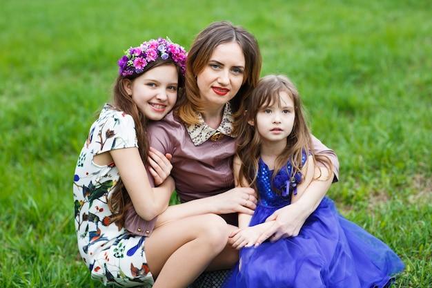 Portret van een jonge moeder en haar twee dochters.