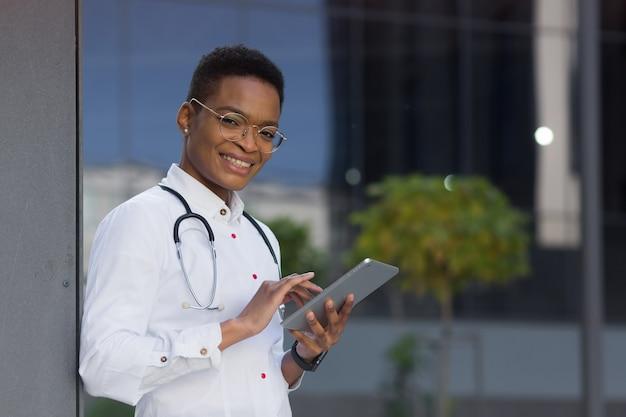 Portret van een jonge, mooie afro-amerikaanse doktersvrouw die lacht en blij naar de camera kijkt en een tablet vasthoudt, voor online consultatie van de patiënt in de buurt van de kliniek