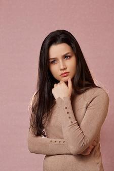 Portret van een jonge mooie aziatische brunette in een lichtbruine trui die over iets denkt