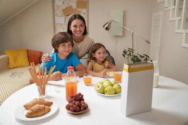 Portret van een jonge, mooie blanke familiemoeder en haar twee schattige kleine kinderen die aan de tafel zitten