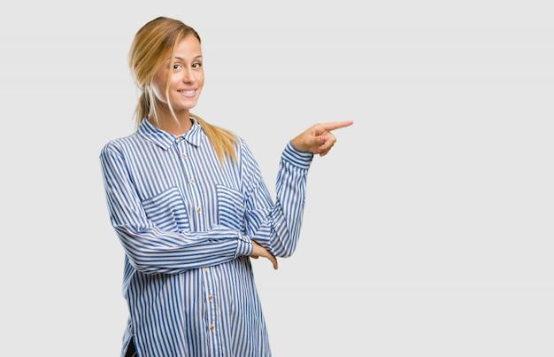 Portret van een jonge mooie blonde vrouw die aan de kant, glimlachend verrast iets presenteert