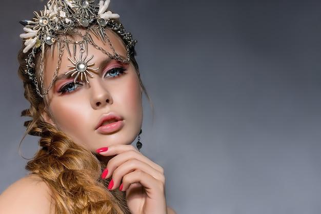Portret van een jonge mooie blonde vrouw, gekleed in een kroon en kostuumjuwelen op een grijze achtergrond close-up.