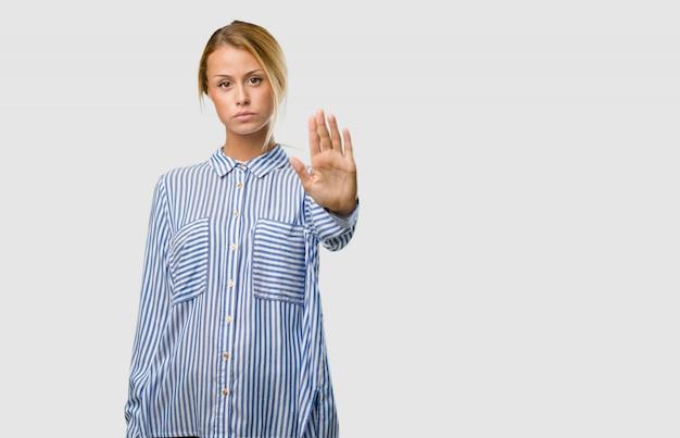 Portret van een jonge mooie blonde vrouw serieus en vastberaden, hand in de voorkant, stop gebaar, ontkennen concept