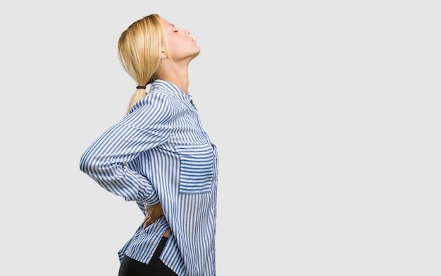 Portret van een jonge mooie blondevrouw met rugpijn toe te schrijven aan spanning op het werk, vermoeid en scherpzinnig