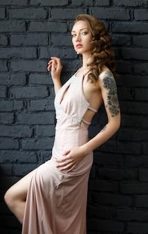Portret van een jonge mooie bruine haired vrouw in een roze kleding.