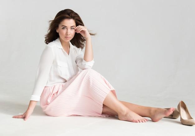 Portret van een jonge mooie bruine haired vrouw in een witte blouse en een roze rokzitting op de vloer