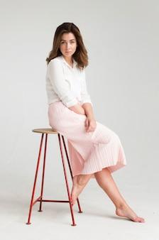 Portret van een jonge mooie bruine haired vrouw in een witte blouse en een roze rokzitting op een stoel