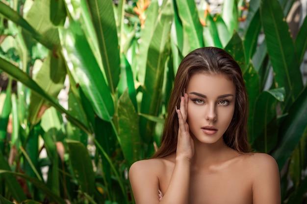 Portret van een jonge mooie brunette vrouw die voor de camera met een hand in de buurt van haar gezicht poseert