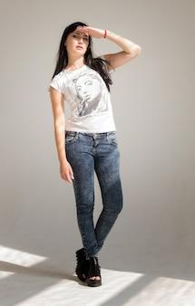 Portret van een jonge mooie brunette vrouw in een wit t-shirt en spijkerbroek