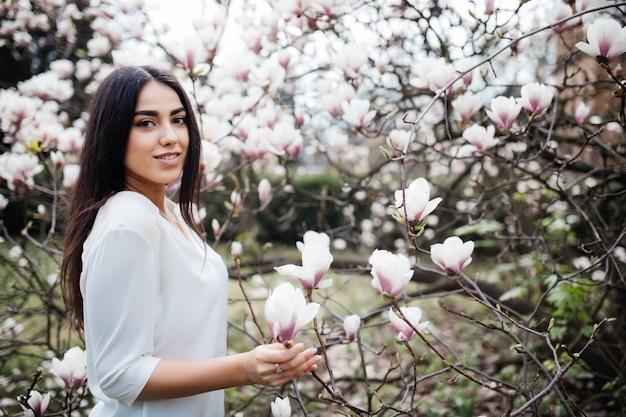 Portret van een jonge mooie dame in de buurt van magnoliaboom met bloemen.