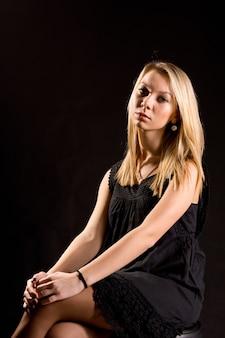 Portret van een jonge mooie elegante blonde vrouw met een ernstige uitdrukking, gekleed in een zwarte feestjurk zittend tegen een donkere achtergrond
