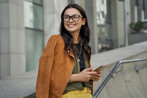 Portret van een jonge, mooie en modieuze vrouw die een bril draagt en haar smartphone vasthoudt
