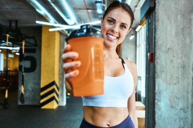 Portret van een jonge, mooie en vrolijke fitnessvrouw in sportkleding die een fles water vasthoudt en naar de camera glimlacht tijdens het sporten in de sportschool. sport, wellness en een gezonde levensstijl