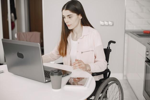 Portret van een jonge mooie gehandicapte vrouw in een rolstoel, thuis werken op een laptop, extern werk.