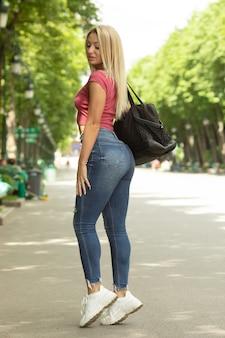 Portret van een jonge mooie glimlachende blonde vrouw buitenshuis