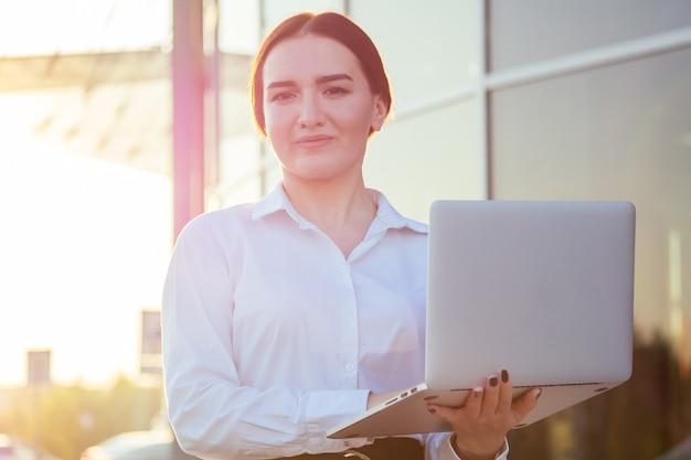 Portret van een jonge, mooie indiase zakenvrouw in kantoorkleding met een noobuk in het zonlicht