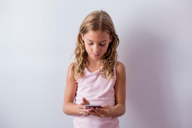 Portret van een jonge mooie jongen met behulp van een mobiele telefoon. witte muur. kinderen binnenshuis. lifestyle