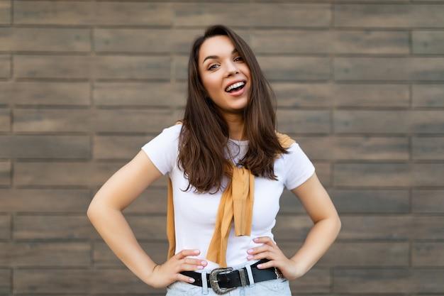 Portret van een jonge, mooie, positieve, gelukkige brunette vrouw die tegen een bruine muur op straat staat en een stijlvolle outfit draagt.