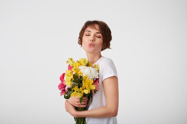 Portret van een jonge mooie schattige kortharige dame in wit t-shirt, met een boeket kleurrijke bloemen, erg blij met zo'n geschenk van haar vriend, stuurt een kus met gesloten ogen over witte muur.