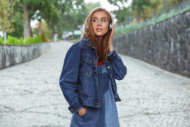 Portret van een jonge mooie tiener die aan muziek luistert