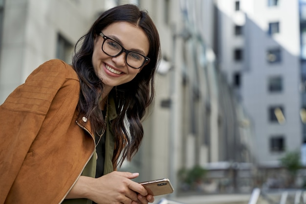 Portret van een jonge, mooie, vrolijke blanke vrouw met een bril die haar smartphone vasthoudt en