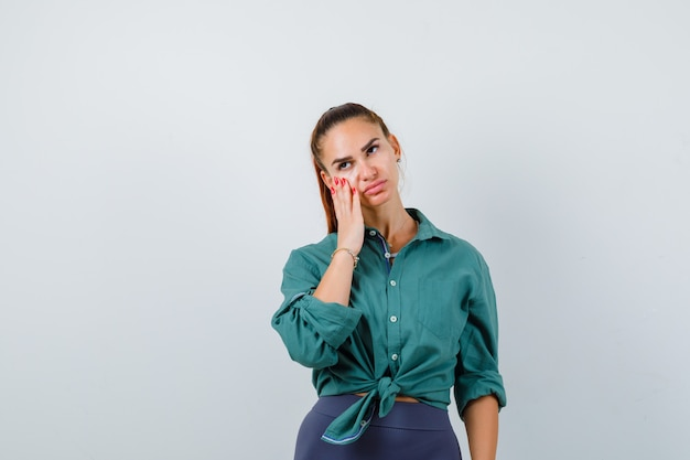 Portret van een jonge, mooie vrouw die de hand op het gezicht houdt in een groen shirt en er peinzend vooraanzicht uitziet