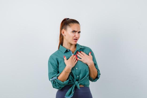 Portret van een jonge, mooie vrouw die de handen op de borst in een groen shirt houdt en besluiteloos vooraanzicht kijkt