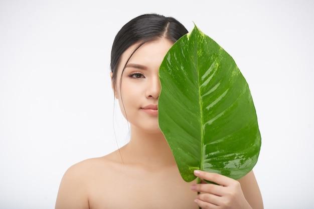 Portret van een jonge mooie vrouw die de helft van haar gezicht bedekt met een groot weelderig blad