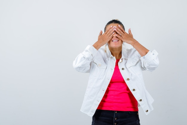 Portret van een jonge, mooie vrouw die de ogen bedekt met de handen in een t-shirt, een witte jas en er nieuwsgierig uitziet aan de voorkant