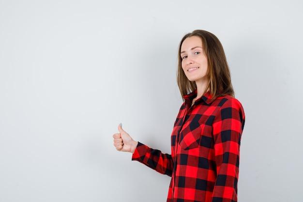Portret van een jonge, mooie vrouw die duim in een casual shirt laat zien en er vrolijk vooraanzicht uitziet