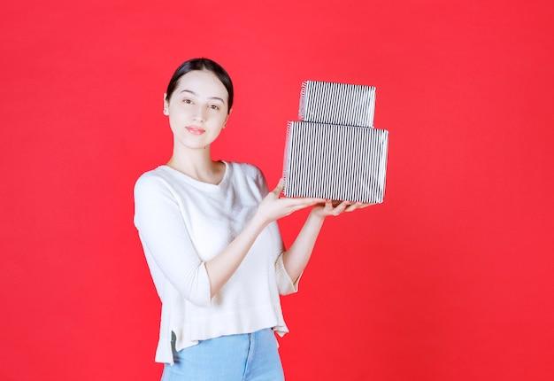 Portret van een jonge, mooie vrouw die een cadeaustapel vasthoudt