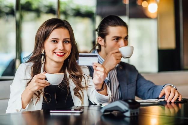 Portret van een jonge mooie vrouw die een creditcard in handen heeft terwijl de man koffie drinkt.