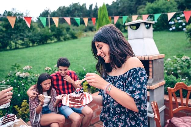 Portret van een jonge mooie vrouw die een fluitje van een cent eet en plezier heeft in een zomerbarbecue in de buitenlucht met zijn vrienden