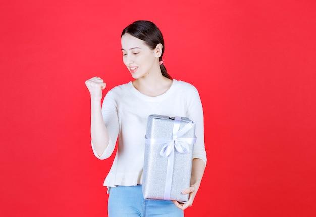 Portret van een jonge mooie vrouw die een geschenkdoos vasthoudt en in haar vuist knijpt