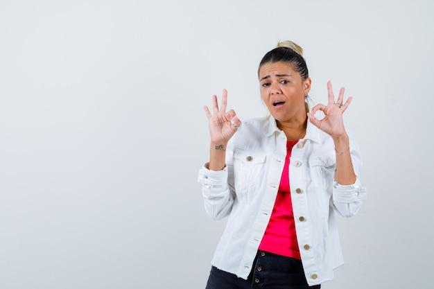 Portret van een jonge, mooie vrouw die een goed gebaar toont in een t-shirt, een witte jas en een verbijsterd vooraanzicht toont
