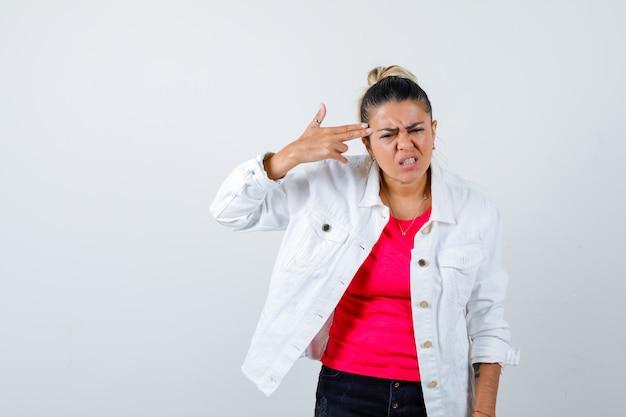 Portret van een jonge, mooie vrouw die een zelfmoordgebaar maakt in een t-shirt, een witte jas en er een geïrriteerd vooraanzicht uitziet